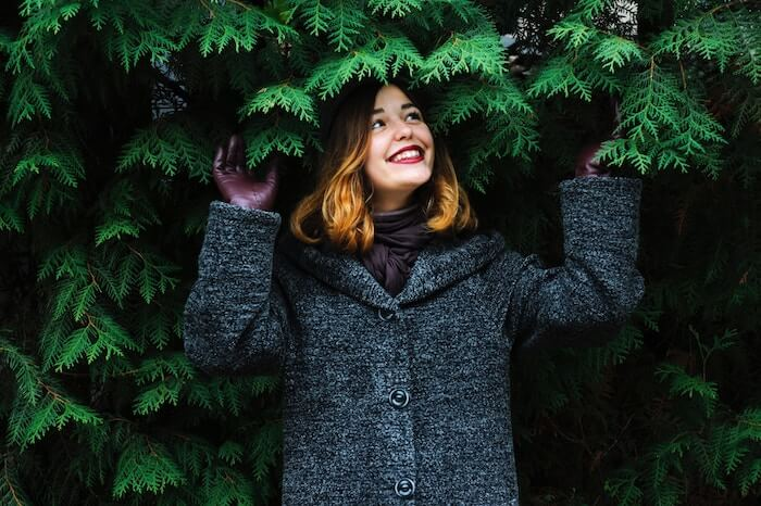 Woman smiling under evergreen tree